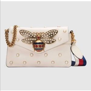 clutch all over pearl studs and metal bee detail.